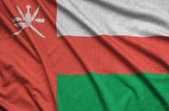 Η σημαία του Ομάν απεικονίζεται σε ένα ύφασμα αθλητικών υφασμάτων με πολλές πτυχές Έμβλημα αθλητικών ομάδων στοκ φωτογραφία