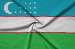 Η σημαία του Ουζμπεκιστάν απεικονίζεται σε ένα ύφασμα αθλητικών υφασμάτων με πολλές πτυχές Έμβλημα αθλητικών ομάδων στοκ φωτογραφία με δικαίωμα ελεύθερης χρήσης