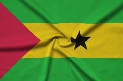 Η σημαία του Σάο Τομέ και Πρίντσιπε απεικονίζεται σε ένα ύφασμα αθλητικών υφασμάτων με πολλές πτυχές Έμβλημα αθλητικών ομάδων στοκ εικόνες με δικαίωμα ελεύθερης χρήσης