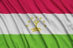 Η σημαία του Τατζικιστάν απεικονίζεται σε ένα ύφασμα αθλητικών υφασμάτων με πολλές πτυχές Έμβλημα αθλητικών ομάδων στοκ εικόνα με δικαίωμα ελεύθερης χρήσης
