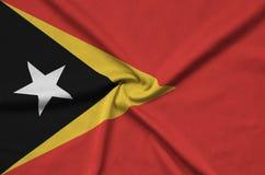 Η σημαία του Τιμόρ Leste απεικονίζεται σε ένα ύφασμα αθλητικών υφασμάτων με πολλές πτυχές Έμβλημα αθλητικών ομάδων στοκ φωτογραφία