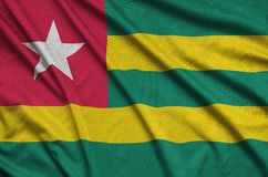 Η σημαία του Τόγκο απεικονίζεται σε ένα ύφασμα αθλητικών υφασμάτων με πολλές πτυχές Έμβλημα αθλητικών ομάδων στοκ εικόνα με δικαίωμα ελεύθερης χρήσης