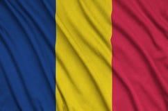 Η σημαία του Chad απεικονίζεται σε ένα ύφασμα αθλητικών υφασμάτων με πολλές πτυχές Έμβλημα αθλητικών ομάδων στοκ εικόνα