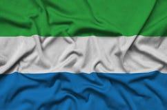 Η σημαία του Sierra Leone απεικονίζεται σε ένα ύφασμα αθλητικών υφασμάτων με πολλές πτυχές Έμβλημα αθλητικών ομάδων στοκ φωτογραφία με δικαίωμα ελεύθερης χρήσης