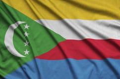 Η σημαία των Κομορών απεικονίζεται σε ένα ύφασμα αθλητικών υφασμάτων με πολλές πτυχές Έμβλημα αθλητικών ομάδων στοκ εικόνες με δικαίωμα ελεύθερης χρήσης