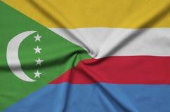 Η σημαία των Κομορών απεικονίζεται σε ένα ύφασμα αθλητικών υφασμάτων με πολλές πτυχές Έμβλημα αθλητικών ομάδων στοκ φωτογραφία με δικαίωμα ελεύθερης χρήσης
