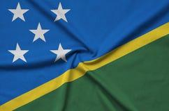 Η σημαία των νήσων του Σολομώντος απεικονίζεται σε ένα ύφασμα αθλητικών υφασμάτων με πολλές πτυχές Έμβλημα αθλητικών ομάδων στοκ εικόνα με δικαίωμα ελεύθερης χρήσης