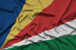 Η σημαία των Σεϋχελλών απεικονίζεται σε ένα ύφασμα αθλητικών υφασμάτων με πολλές πτυχές Έμβλημα αθλητικών ομάδων στοκ φωτογραφία