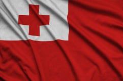 Η σημαία των Τόνγκα απεικονίζεται σε ένα ύφασμα αθλητικών υφασμάτων με πολλές πτυχές Έμβλημα αθλητικών ομάδων στοκ φωτογραφία με δικαίωμα ελεύθερης χρήσης