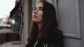 Η σκέψη γυναικών και απολαμβάνει το καθαρό αέρα που κλίνει στον τοίχο απόθεμα βίντεο