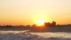 Η σκηνή ηλιοβασιλέματος της χαλάρωσης ατόμων σε διογκώσιμο στην παραλία φιλμ μικρού μήκους
