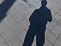 Η σκιά ενός ατόμου σε ένα κεραμίδι πεζοδρομίων σε ένα πάρκο στοκ εικόνα