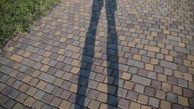Η σκιά ενός ατόμου στο δρόμο που στέκεται στα πόδια του απόθεμα βίντεο