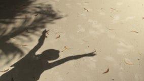 Η σκιά μιας γυναίκας στο καπέλο απεικόνισε στην άμμο στην παραλία απόθεμα βίντεο