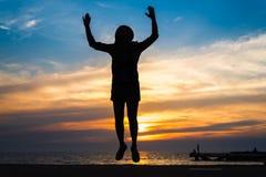 Η σκιαγραφία άλματος κοριτσιών στη θάλασσα με τον ουρανό backgrouund Στοκ εικόνες με δικαίωμα ελεύθερης χρήσης