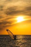 Η σκιαγραφία αέρας-surfer-τυλίγει στο ηλιοβασίλεμα κυμάτων Στοκ Εικόνα