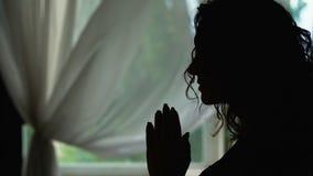 Η σκιαγραφία γυναικών που προσεύχεται στο εσωτερικό, ανάγνωση προσεύχεται με τα χέρια που διπλώνονται, ρωτώντας το Θεό απόθεμα βίντεο