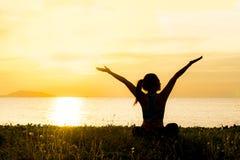 Η σκιαγραφία γυναικών τρόπου ζωής γιόγκας περισυλλογής στο ηλιοβασίλεμα θάλασσας, χαλαρώνει ζωτικής σημασίας