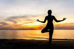 Η σκιαγραφία γυναικών τρόπου ζωής γιόγκας περισυλλογής στο ηλιοβασίλεμα θάλασσας, χαλαρώνει ζωτικής σημασίας Στοκ Φωτογραφία