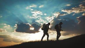 Η σκιαγραφία δύο ανθρώπων στην κορυφή του βουνού με τα σακίδια πλάτης και άλλου εργαλείου που εκφράζει την ενέργεια και την ευτυχ απόθεμα βίντεο