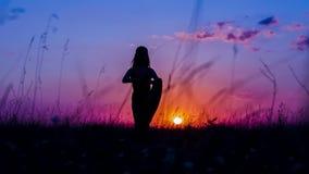 Η σκιαγραφία ενός νέου κοριτσιού που κάνει το δέντρο γιόγκας θέτει