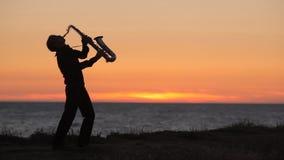 Η σκιαγραφία ενός saxophone παιχνιδιού μουσικών επάνω φιλμ μικρού μήκους