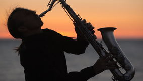 Η σκιαγραφία ενός saxophone παιχνιδιού μουσικών επάνω απόθεμα βίντεο