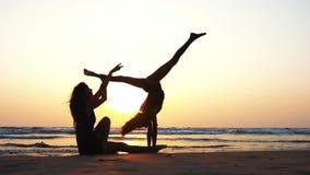 Η σκιαγραφία μιας γυναίκας εκπαιδεύει ένα κορίτσι για να εκτελέσει το ακροβατικό στοιχείο στην παραλία απόθεμα βίντεο