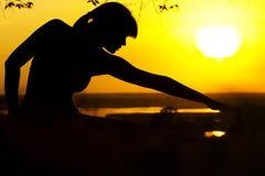 Η σκιαγραφία μιας γυναίκας συμμετείχε στην ικανότητα στη φύση στο ηλιοβασίλεμα, ένα αθλητικό θηλυκό σχεδιάγραμμα, την έννοια του  Στοκ εικόνες με δικαίωμα ελεύθερης χρήσης