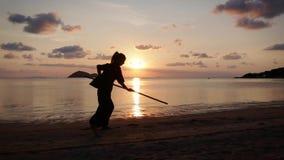 Η σκιαγραφία μιας νέας ισχυρής γυναίκας στην παραλία που κάνει ένα kung-fu ασκεί