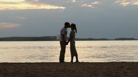 Η σκιαγραφία μιας νεολαίας συνδέει ερωτευμένο στο ηλιοβασίλεμα Το κορίτσι στάθηκε tiptoe και φιλά ήπια τον τύπο στην ακτή της λίμ απόθεμα βίντεο