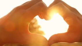 Η σκιαγραφία παραδίδει τη μορφή της καρδιάς με τις ακτίνες του ήλιου ρύθμισης απόθεμα βίντεο