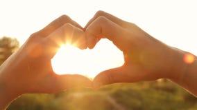 Η σκιαγραφία παραδίδει τη μορφή της καρδιάς με τις ακτίνες του ήλιου ρύθμισης φιλμ μικρού μήκους