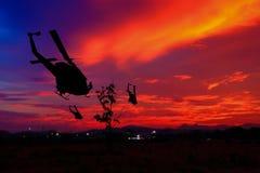 Η σκιαγραφία στρατιωτών αναρριχείται κάτω από το ελικόπτερο στο ηλιοβασίλεμα, η εχθροπραξία στάσεων έννοιας με το διάστημα αντιγρ Στοκ Φωτογραφία