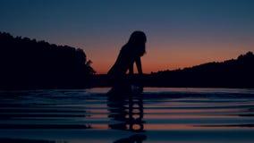 Η σκιαγραφία της γυναίκας στέκεται το γόνατο βαθιά στη λίμνη στο ηλιοβασίλεμα και καταβρέχει το νερό απόθεμα βίντεο