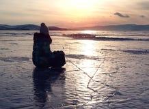 Η σκιαγραφία της ευτυχούς γυναίκας ελευθερίας με τα όπλα η απόλαυση της θέας του ηλιοβασιλέματος στην παγωμένη Baikal λιμνών επιφ Στοκ εικόνες με δικαίωμα ελεύθερης χρήσης