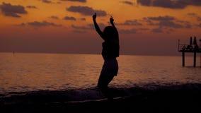 Η σκιαγραφία της ευτυχούς λεπτής γυναίκας πηδά σε μια παραλία στο χρόνο βραδιού μετά από τα χέρια ηλιοβασιλέματος και αύξησης απόθεμα βίντεο