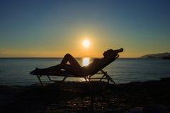Η σκιαγραφία της νέας γυναίκας βρίσκεται στο deckchair στο ηλιοβασίλεμα στοκ φωτογραφίες