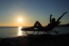 Η σκιαγραφία της νέας γυναίκας βρίσκεται στο deckchair στο ηλιοβασίλεμα στοκ εικόνες