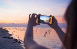 Η σκιαγραφία της νέας γυναίκας με την κινητή τηλεφωνική κάμερα που παίρνει την εικόνα του όμορφου τοπίου ηλιοβασιλέματος παραλιών στοκ εικόνα
