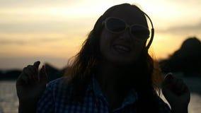 Η σκιαγραφία της νέας γυναίκας που φορά τα ακουστικά έχει τη διασκέδαση χορεύει μουσική ακούσματος στην παραλία στο καταπληκτικό  απόθεμα βίντεο