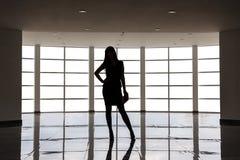 Η σκιαγραφία της νέας ελκυστικής γυναίκας που ντύνεται στο επιχειρησιακό κοστούμι με μια κοντή φούστα στέκεται ενάντια στο μεγάλο στοκ εικόνες με δικαίωμα ελεύθερης χρήσης