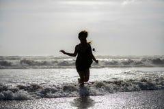 Η σκιαγραφία της νέας ευτυχούς ασιατικής γυναίκας χαλάρωσε την εξέταση τα άγρια κύματα θάλασσας στην τροπική παραλία ηλιοβασιλέμα Στοκ Εικόνες