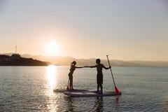 Η σκιαγραφία του αρσενικού και το θηλυκό στην κυματωγή γουλιάς τραβούν τα χέρια μαζί στον ωκεανό Τρόπος ζωής έννοιας, αθλητισμός, Στοκ Εικόνα
