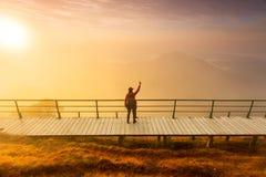 Η σκιαγραφία του ατόμου κρατά ψηλά τα χέρια στην αιχμή του βουνού, έννοια επιτυχίας στοκ φωτογραφία με δικαίωμα ελεύθερης χρήσης