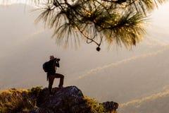 Η σκιαγραφία του ατόμου κρατά ψηλά τα χέρια στην αιχμή του βουνού, έννοια επιτυχίας στοκ εικόνα με δικαίωμα ελεύθερης χρήσης