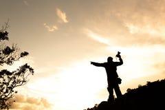 Η σκιαγραφία του ατόμου κρατά ψηλά τα χέρια στην αιχμή του βουνού, έννοια επιτυχίας στοκ εικόνες