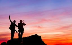 Η σκιαγραφία του ατόμου κρατά ψηλά τα χέρια στην αιχμή του βουνού, έννοια επιτυχίας στοκ εικόνα