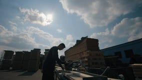 Η σκιαγραφία του βιομηχανικού νέου εργαζομένου ξυλουργών φορά τα προστατευτικά δίοπτρα και τη χρησιμοποίηση μιας κατασκευής στην  απόθεμα βίντεο