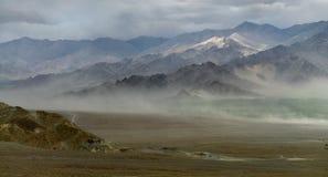Η σκιαγραφία του βουνού κατά τη διάρκεια μιας θύελλας σκόνης, τοίχος άμμου δημιουργεί την ελαφριά ομίχλη και το ταξίδι κατά μήκος Στοκ Εικόνα